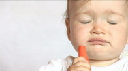 Baby sits at a table and eats a carrot Stock Footage