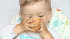 Small child eats bread behind a table Stock Footage