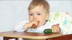 Baby sits at a table and eats a carrot - stock footage
