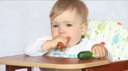 Stock Video Footage of Baby sits at a table and eats a carrot