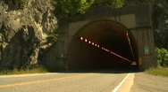 Traffic entering and exiting highway tunnel  Stock Footage
