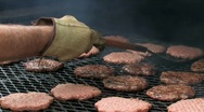 Chef cooking hamburgers on a large barbecue grill Stock Footage