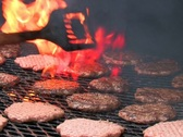 Stock Video Footage of Chef cooking hamburgers on a large flaming barbecue grill