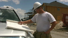 House Builder Looking At Plans On The Hood Of His Truck - stock footage
