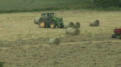 Hay baler passes tractor picking up bales on forks Stock Footage