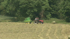 Tractor towing hay baler at work. Stock Footage
