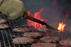 Flipping hamburgers on a flaming barbecue grill Stock Footage