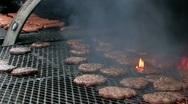 Hamburgers and hot dogs on flaming grill Stock Footage