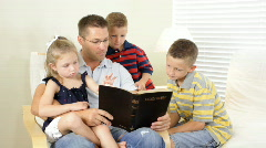 Dad reading bible to kids Stock Footage