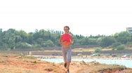 Stock Video Footage of Young beautiful girl play in sports. She runs on sea coast