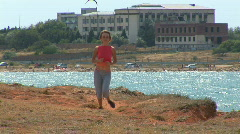 Young beautiful girl play in sports. She runs on sea coast Stock Footage