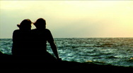 Loving couple sits on seacoast. Stock Footage