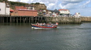 Stock Video Footage of Old lifeboat now used for holiday sailing trips entering Whitby harbor Yorkshire