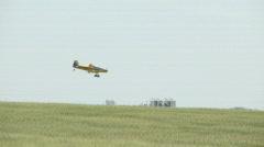 Agplane flying low over crop applying herbicide Stock Footage