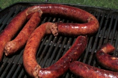 Cook turns sausage on a barbecue grill Stock Footage