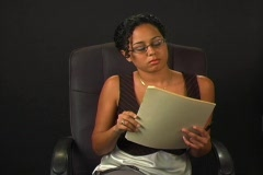 Beautiful Young Woman in an Office Chair with a File Folder Stock Footage