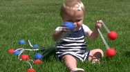 Vid034 baby girl playing with ladder balls in grass Stock Footage