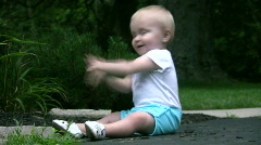 Vid038 baby playing in mulch on driveway Stock Footage