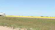 Stock Video Footage of Highway Truck rolling by Canola field 001