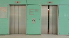 Businessteam of three out of elevator TWO TAKES Stock Footage