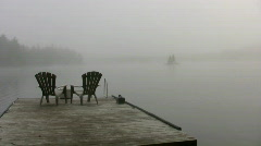 dock stretches out into foggy lake  - stock footage