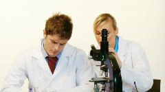 Male and female scientist looking through a microscope Stock Footage