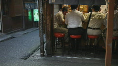 Japanese men eating in small restaurant Stock Footage