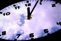 Clock in time-lapse loop with fast moving clouds in the background - stock footage