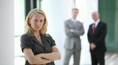 Serious looking businesswoman with blurred men in back Stock Footage