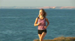 Girl runs against the sea! It the sportswoman. Clouse-up Stock Footage