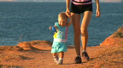 Mother and the child go on seacoast. The child learns to go independently Stock Footage