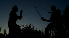 men at sunset fighting with swords - stock footage