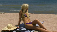 Blond at Beach Puts on Hat 01 - stock footage