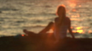 Lonely girl sits on seacoast and looks in at a sunset 3 Stock Footage