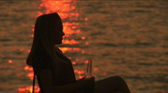 The girl drinks sitting on a armchair. Sunset Stock Footage