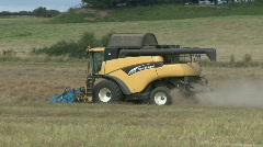 New Holland combine harvester gathers previously cut Rape Seed Stock Footage