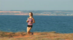The young woman plays sports against the sea. She runs Stock Footage