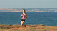Stock Video Footage of The young woman plays sports against the sea. She runs