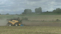 New Holland combine harvester gathers previously cut Rape Seed. Stock Footage
