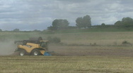 Stock Video Footage of New Holland combine harvester gathers previously cut Rape Seed.