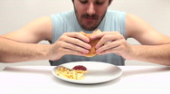 Young man eats burger and fries in fast motion - HD  Stock Footage