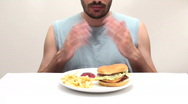 Young man eats burger and fries - HD  Stock Footage