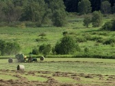 Hay bailer ejects a hay bail as Farmer makes hay in evening sun Stock Footage