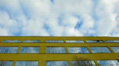 Over the yellow house clouds float and are reflected in house windows Stock Footage
