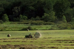 Hay bailer ejects a hay bail as Farmer makes hay in evening sun - stock footage