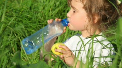 Girl drinking water from  bottle and eating apple Stock Footage