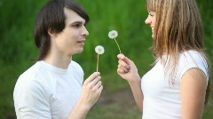 Young man and girl blowing flowers, facing  each other Stock Footage