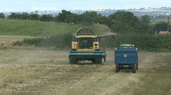 New Holland combine harvester starts to unload Rape Seed - stock footage