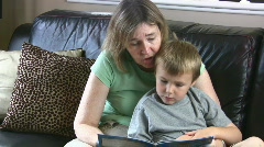 Grandma Reading A Book To Her Grandson Sat On The Sofa Stock Footage
