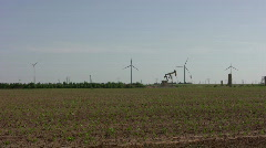 Wind mill farm and oil well pumping 1 Stock Footage